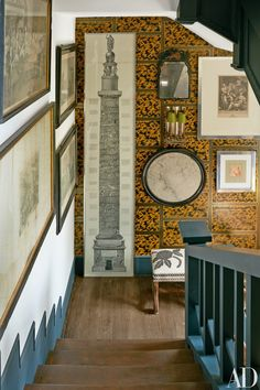 The stairway hosts a towering Piranesi print, a small William and Mary mirror, and a Regency-style stool upholstered in an embroidered fabric | archdigest.com