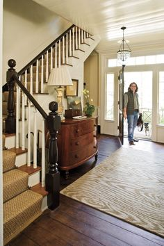 Jamie McPherson created an inviting entry in his central stair hall with a burled-mahogany, bow-front chest and faux- bois patterned rug.