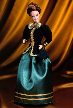 """Collector Edition  Release Date: 1/1/1996  Product Code: 15621    A nostalgic Hallmark greeting card comes to life with this charming and demure holiday Barbie® doll. Her dark green velvety jacket is accented with opulent golden trim. An emerald green satin skirt billows out beneath the jacket while a golden bow and shimmering """"brooch"""" add a festive holiday accent. From her strawberry blonde hair, piled elegantly atop her head, to her velvety handbag and matching green pumps, Yuletide…"""