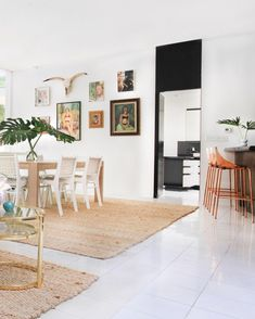 Feast Your Eyes: Gorgeous Dining Room Decorating Ideas - The neutral furniture and jute area rugs enhance the dining area without overwhelming it with patterns. The understated design also showcases the bright green plants and copper accent bar stools.