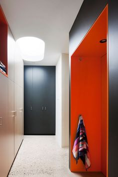 This modern laundry room has floor to ceiling cabinets, and brightly colored orange pockets of open storage areas.