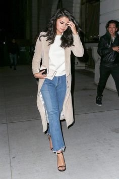 Selena Gomez wears a white top, suede coat, cropped jeans, and black sandals