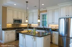 A window over the sink allows front views and natural light in this kitchen. The Whitcomb #1218-D.