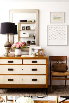 Wood and white dresser styled with lamp, mirror, and flowers