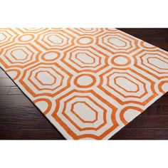 Hand-tufted in polyester, this rug features colors of burnt orange and ivory. Its unique design makes this rug perfect for any home. Designed by Angelo Surmelis.