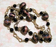 Vintage Mid Century Venetian art glass beaded necklace Black wedding cake beads bordered by round black beads and decorative gold tone knotted rope links Connected by decorative metal link connectors Screw barrel clasp 32 inches long Each glass bead is 5/8 diameter Good vintage condition, no cracks or other damage to the beads I specialize in vintage beaded jewelry, please visit my store for more offerings International buyers welcome, overcharges are refunded Priority shipping is option...