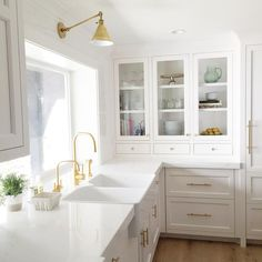 Stunning kitchen features white shaker cabinets adorned with long brass pulls topped with white quartz countertops fitted with a dual apron sink and two gold gooseneck faucets situated under window illuminated by a Boston Functional Library Wall Light in Antique Brass.