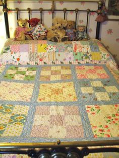 Love the prints in this quilt - and the darling bears and the brass bed.  By the vintage cottage