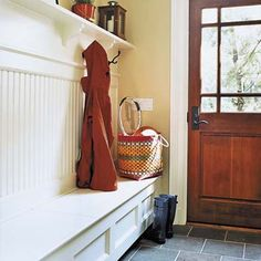 Entry/mudroom storage bench idea with space to tuck the toes of shoes and boots under the bench. The bench has a hinged lid for storage of outdoor play gear, etc.