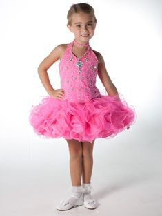 $350.00 Cute Unique Fashion Pageant Dress UF1067. This pageant dress has a halter neckline with a beaded thin necklace, gorgeous beaded and embroidered bodice, and a basque waistline. A cupcake short ruffled skirt completes the look to this pageant dress. This adorable dress will make your little pageant girl a star!