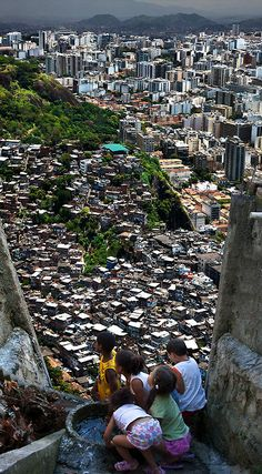 "photos from claudia jaguaribe's ""between hills"" (2012) of rio de janeiro, as seen from the (no doubt intentionally claustrophoic) perspective of children in the favelas who can see the more affluent apartment complexes in the background"