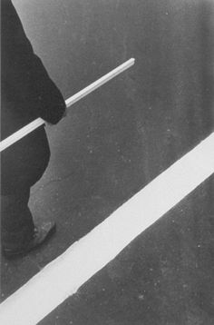 Ralph Gibson - Deja Vu, 1976 Gibson's compositions are often deliberately enigmatic. Subjects are cropped and the photographer is clearly interested in upsetting our conventional ways of seeing things. Here, a man carrying a white piece of wood (?) unconsciously echoes the white stripe of the road markings.