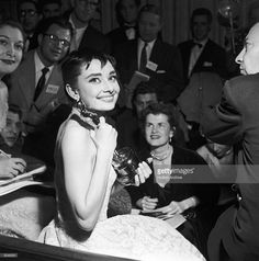 Belgian-born actor Audrey Hepburn (1929 - 1993) is surrounded by reporters as she holds the Best Actress Oscar she won for her role in director William Wyler's film, 'Roman Holiday,' at the Academy Awards ceremony in New York City.  (Photo by Hulton Archive/Getty Images)