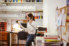 Businesswoman at phone working in her office. by BONNINSTUDIO | Stocksy United
