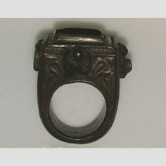'Papal' ring  Italy  15th century  Bronze ring (gilding now lost), the square bezel set with green paste, the sides with the Evangelists' symbols in relief, a crown and shield of arms at the shoulders and bearing the inscription RAGONAS  18 mm internal ring diameter; 165.5 g weight