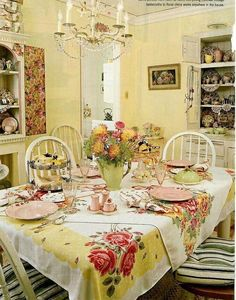 "Yellow Dining Room:  A double layer of tablecloths are on the table.  Keep in mind if you have an undersized, yet favorite tablecloth you want to use.  In this photo, both tablecloths are pretty and decorative, but a solid colored tablecloth could be used as a base, topped with the cloth that is to be ""showcased"".  Great idea!"