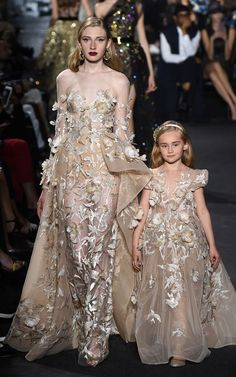 Like the asymetric draping on the overskirt plus the 3 dimension embellishment is stunning. A flesh-tone lining (even a semi sheer one) would prevent the transparency detracting from the impact of the incredible fabric and its construction. But, there's NEVER a reason to make a child's dress so sheer her body can be seen through a transparent outer fabric. Use a flesh tone lining!