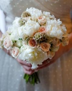 Soft clutch of peonies, spray roses, and scabiosa pods