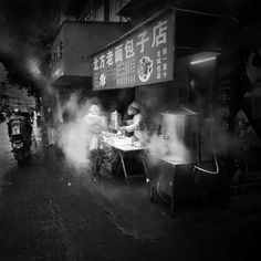 A woman buys steamed bread in a back alley on a cold, rainy, February morning.  Liuzhou, Guangxi, China.