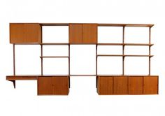 This large Royal teak wall unit was designed by Poul Cadovius and manufactured by Cado in about 1960 in Denmark. The modular system can be assembled as desired and features large cabinets with plenty of storage space. In a good vintage condition. Measurements of the individual parts: 3x cabinets with sliding doors: 80 x 51 x 46 cm; 2x cabinets with sliding doors: 80 x 24 x 56 cm; 1x desk unit with drawers: 80 x 11 x 46 cm; 1x shelf: 80 x 38 cm; 9x shelves: 80 x 22 cm; 6x wall mounts: ca…