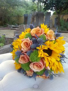 Bridal bouquet by Fleurt Floral Art of sunflowers, roses, eryngium and green ball dianthus.
