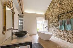 Une salle de bain très design avec une baignoire-îlot au milieu. A droite un mur de pierre apparente. A gauche, une vasque noire arrondie.