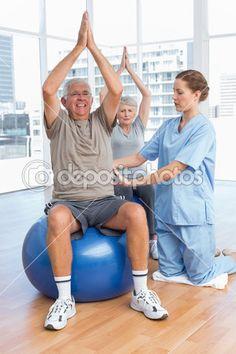 vrouwelijke therapeut helpen senior koppel met oefeningen in de medische kantoor — Stockbeeld #42922489