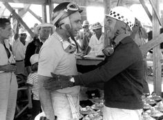 Juan Manuel Fangio and Jean Behra share a happy moment as team mates for what will eventually be the winning car in the 1957