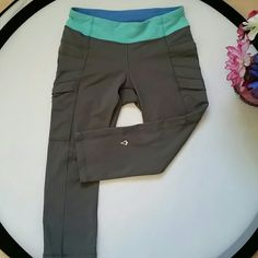 """Ivivva pants Size 10 in kids which is like a 0 or 2 in women. In pre loved conditions.  Gray with aqua blue waistband.  Back zippered pouch.  Inseam about 17"""".  Small pockets on both sides. ivivva  Pants Capris"""