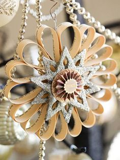 """silver star ornament: cut thin strips of newspaper or from a book page. Loop each strip until you have enough to form a circle; hot-glue together in the center. Add glittery chipboard stars in the middle for subtle shine."""