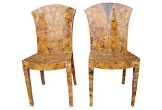 "Sramatic pair of ""his and hers"" chairs created with inlaid horn, inlaid brass accents and brass feet. One chair has a design on the back in dark horn."