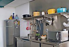 Sobre a pia, a prateleira de metal dá suporte às panelas, na casa dos chefs de cozinha Jefferson e Janaína Rueda. Os dois queriam uma cozinha como as dos restaurantes. Por isso, o aço inox é o material predominante no ambiente