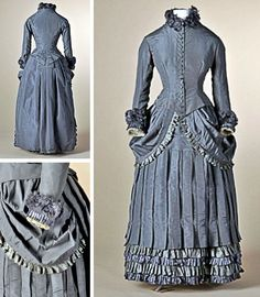 Dress of gray-purple taffeta silk, ca. 1883. Around 1879, hiplines began to be curved again, and by 1883 they had become small platforms supported by ½ hoops. This dress has skirt w/drapery that expands at hips. Inside, bustle can be made rounder or flatter w/laces. Skirt has vertical pleats & is finished at bottom w/green & gray horizontal plissé bands. Waisted bodice with button closure ends in back in point w/flat pleats. High collar & cuffs trimmed w/bands of ravelling. Mode Museum…