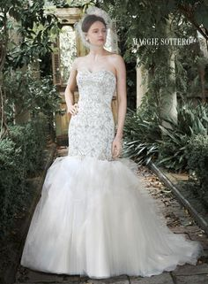 Intricate patterns of glittering Swarovski crystals, pearls and sequins adorn the dropped bodice of this fit and flare wedding dress, with dramatic tulle skirt and sweetheart neckline. Finished with crystal buttons over zipper and inner corset closure.  Maggie Sottero Bridal - 5MT710-Kennedy