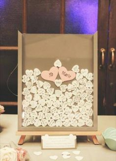Wedding Guest Book Idea - Have guests sign little wooden hearts and drop them into a shadow box.