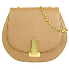 Show off your feminine side with this petite purse. Crafted in smooth calf leather, it hangs from a gold-hued chain and features a fold-over flap with flip-lock closure.