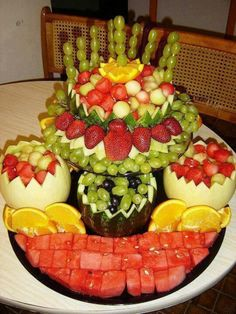 Golden pineapple, Honeydew, orange slices, mango, green grapes, kiwi, cantaloupe.  Everything but red makes it a Golden Anniversary fruit tower.