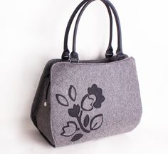 Make your travelling convenient by carrying this grey felt handbag. Made from felt, this handbag offers ample space to dump your essentials in it safely. Further, this handbag has twin handles and floral detailing. This felted handbag that is a perfect pick for women on the go. Spacious in design, this bag will allow you to keep your belongings with ease. #purse #handbag #feltbag