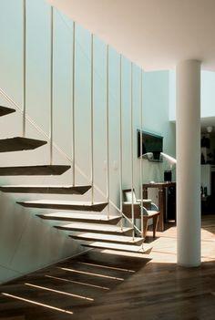 A escada para a área íntima tem degraus de jatobá maciço com forma de asas fixados de um lado da parede e, do outro, suspensos por tirantes de ferro. Projeto do arquiteto Luciano Devià