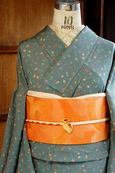スモークがかった、ほのかに青みをおびた淡く優しい緑色の地に、三味線や琵琶、小太鼓に横笛、笙の笛などの楽器や、扇子や和綴じ本などのモチーフが、まるで玩具のように愛らしい雰囲気で染め出された縮緬袷着物です。 Apron, Kimono, Fashion, Moda, Fashion Styles, Kimonos, Fashion Illustrations, Aprons