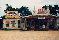 """A cross roads store, bar, """"juke joint,"""" and gas station in the cotton plantation area, Melrose, La. Photographed by Marion Post Wolcott in June of 1940.Summary: Photograph shows Sign on left building:"""