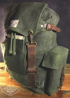 We introduce you to The Globetrotter Pack. This is a really big hand waxed canvas and leather backpack and is perfect for your bushcraft, hiking, camping or travel bag. The style is inspired in vintage military and camping bags. Olive green waxed cotton canvas, brown genuine cowhide leather straps and beige cotton waxed canvas lining. Holds an extra pair of shoes or boots in the front, and its side pockets can hold a big water bottle each. You can even take your laptop with you inside its…