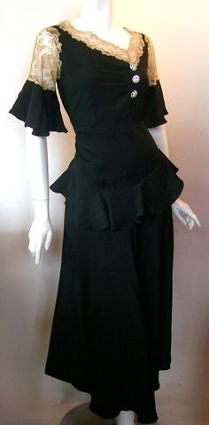 Black silk crepe 30s dress with ecru lace trim, asymetrical  neckline and rhinestone button accents. Dramatic ruffle at sleeve cuffs and hip