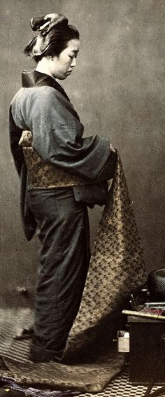Putting on an obi (wide belt).  Hand-colored photo, 1870s, Japan // by photographer Felice Beato