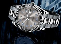 Datejust II (Reference: 116334). Description: 41mm Rolesor case in stainless steel with 18K white gold fluted bezel, grey dial, blue Arabic numerals, and stainless steel Oyster bracelet with Oysterclasp and Easylink extension link. Water resistant to 100 meters.