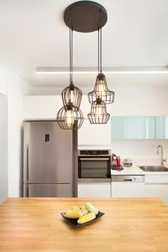 Cozinha com bancada em ilha com tampo de madeira, geladeira inox, armários brancos e luminária pendente preta aramada. Apartamento Contemporâneo em Israel  por Dana Shaked