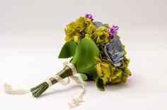 1967 Bouquet.  Elaborado con 8 flores en tela vaquera y otras 8 en fieltro, mezcladas con preservadas verdes, forman un ramo evocador del famoso Summer of Love, concierto hippie de 1967. Es un ramo de cerca de cuarenta centímetros de diámetro, que finaliza en un mango forrado en parte en lazo de raso verde y adornado con cinta.