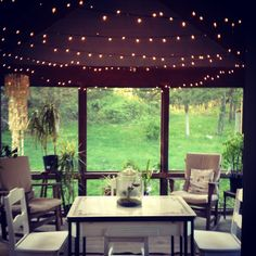 Small screened porch with lights and enamel table, white Art Deco chairs.