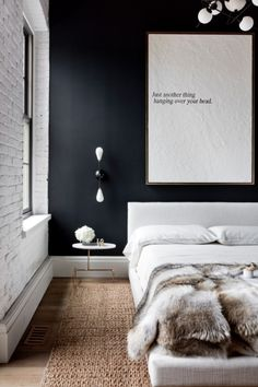 upholstered bed + navy wall + white painted brick + fur throw + minimal art