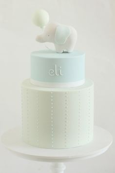 hello naomi first birthday cake light blue with elephant topper holding a balloon